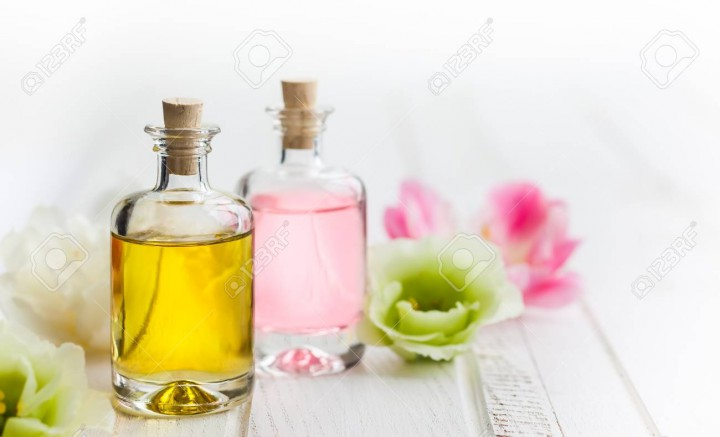 Bottles with essential aroma oil and flowers on white wooden background. Healthy skin care. Place for text.
